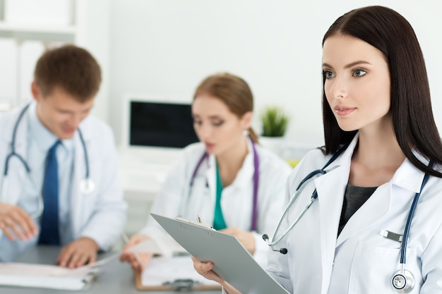 Portrait of brunette female medicine doctor holding document folder with two her colleagues working. healthcare and medicine concept.