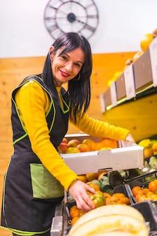 Portrait of brunette fruit girl working ordering fruits in a greengrocer establishment, vertical photo