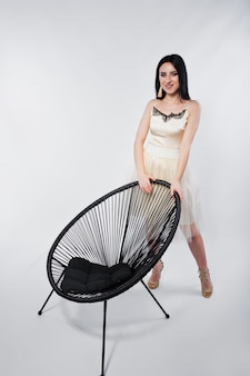 Portrait of brunette girl on beige dress with chair isolated on white.