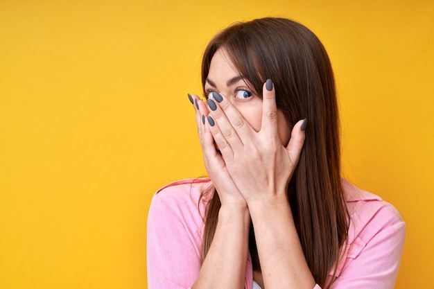 Portrait of brunette girl covering her eyes isolated on yellow background, looking through fingers, peeping at the camera, afraid to watch