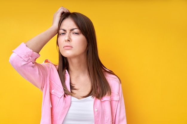 Portrait of brunette girl holding her head with hand, thinks and doubts, makes decision, squints isolated on yellow background, difficult choice