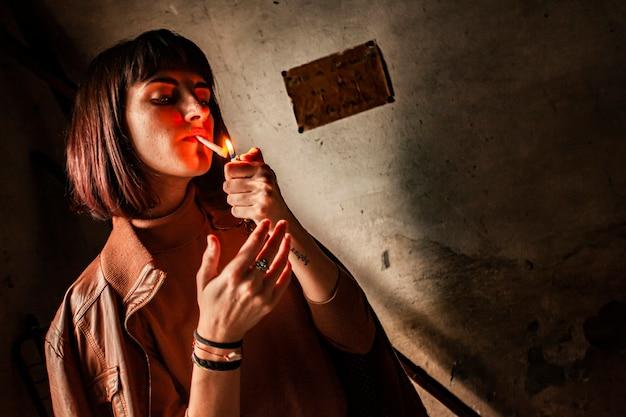 Portrait of a brunette girl lighting a cigarette 14
