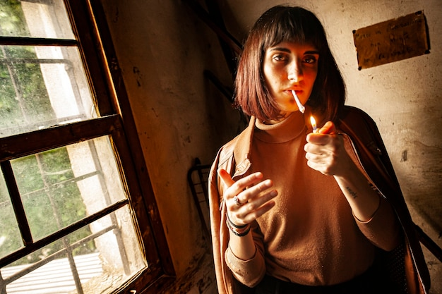 Portrait of a brunette girl lighting a cigarette 9