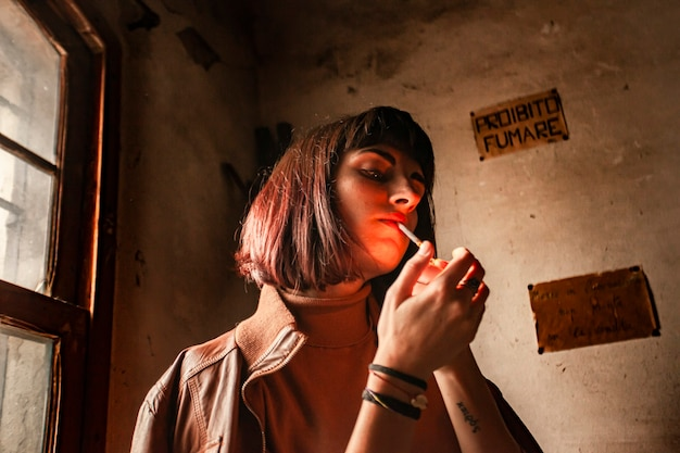 Portrait of a brunette girl lighting a cigarette in an old and abandoned house