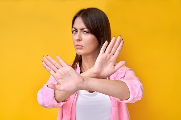 Portrait of brunette girl showing stop gesture, no please, you are refused isolated on yellow