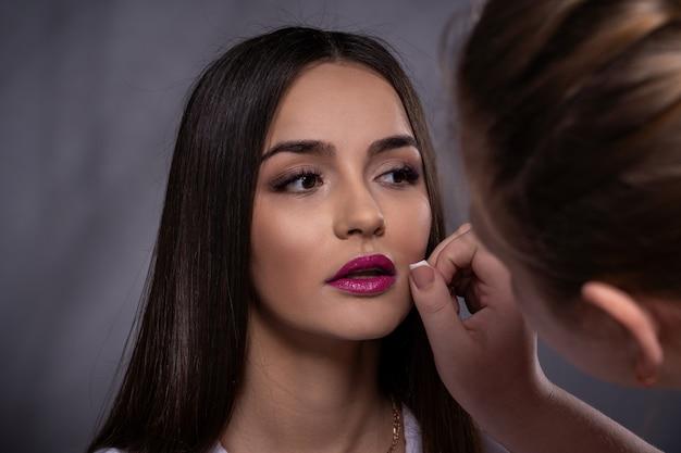 Portrait of brunette girl in the studio, correct makeup preparation
