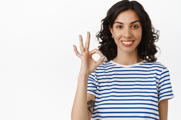 Portrait of brunette girl with white perfect smile, shows okay ok gesture, approve and like, agree or say yes, standing in t-shirt on white.