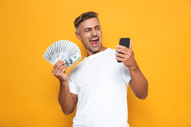 Portrait of brunette guy 30s in white t-shirt holding cell phone and bunch of money isolated on yellow