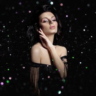 Портрет брюнетки с шикарными пышными волнистыми волосами, пухлыми губами, блеском боке. натуральная косметика и красивый яркий макияж на лице девушки, крепкие волосы.