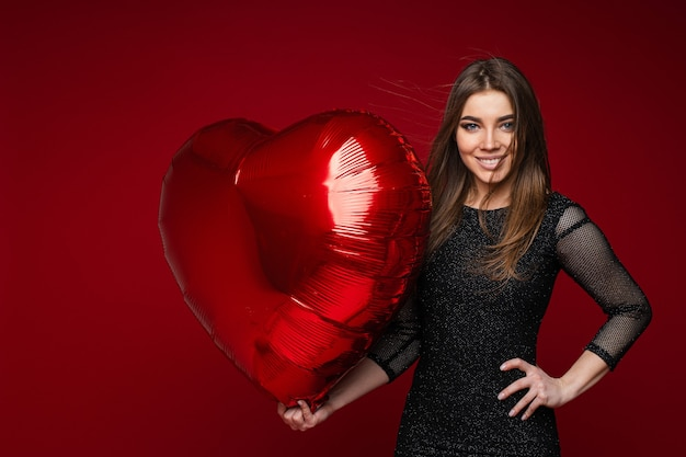 Portrait of brunette lady in dark cocktail dress with a red air balloon in shape of heart with arm on waist. smiling at camera on red background.