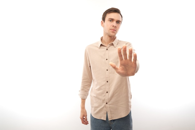 Portrait of brunette man in casual showing stop gesture, no please, you are refused isolated on white studio background
