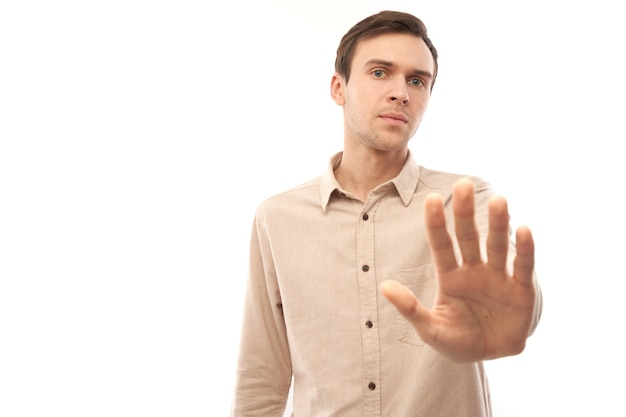 Portrait of brunette man in casual showing stop gesture, no please, you are refused isolated on white