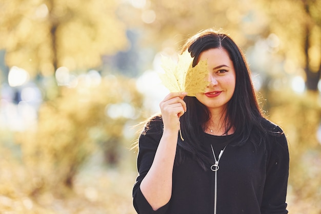 Portrait of brunette that have fun with leaves in beautiful autumn park.