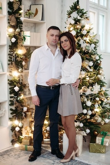 Portrait of brunette wife and husband in elegant clothes embracing by decorated christmas tree with garland and christmas balls at home