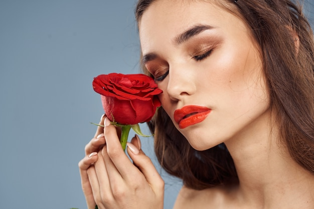 Portrait of a brunette with red lipstick on her lips, beautiful woman with a rose