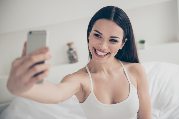 Portrait of brunette woman on the bed with phone