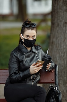 Portrait of brunette woman in a black protective mask sitting on a bench in the park, sunny spring day. woman talking on mobile phone