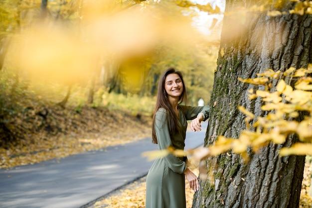 Portrait of brunette woman in green dress posing in autumn park