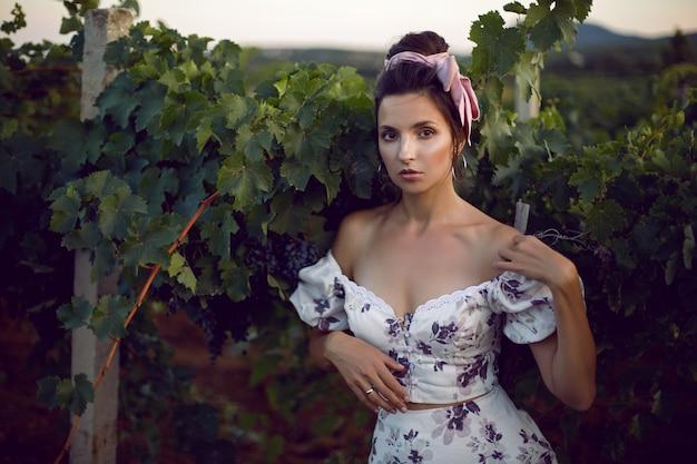 白いドレスを着た肖像画のブルネットの女性は、イタリアの夏のブドウ園に立っています