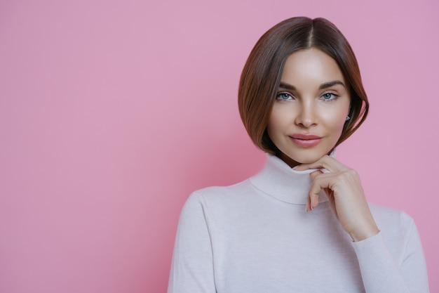 Portrait of brunette woman keeps hand on collar of turtleneck, has healthy perfect skin