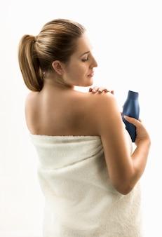 Portrait of brunette woman using creme after shower
