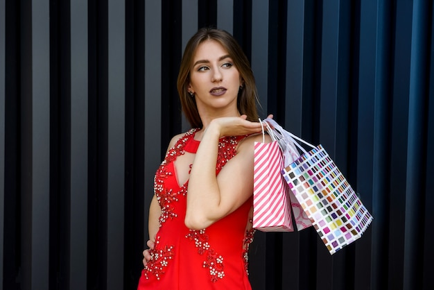 Portrait of brunette woman with gift bags in elegant red dress. celebration concept