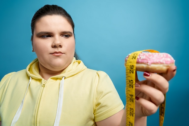 Portrait of brunette woman in yellow sweater looking at sweet donut with pink glaze and measuring tape on it, keeping on her hand.young female is thinking about to lose weight and do not eat trans fat