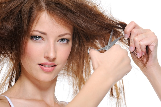 Portrait of brunette young woman cutting her hair isolated on white