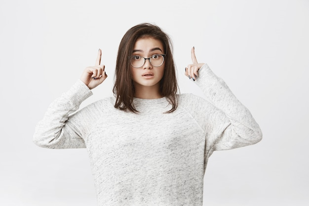 Portrait of brunette young woman in glasses pointing up