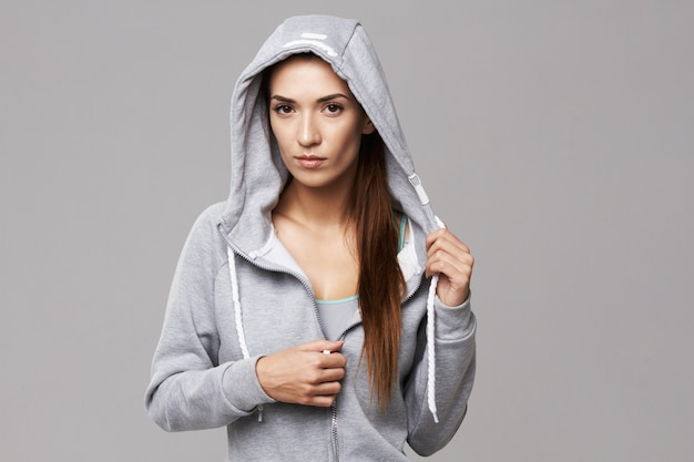 Portrait of brutal athletic woman in hood and sportswear on white.