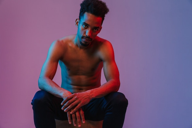 Portrait of brutal handsome shirtless african american man sitting crossed isolated over violet wall