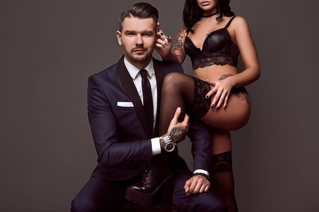 Portrait of a brutal man in elegant suit touches sexy girl with a tattoo in lingerie on gray background
