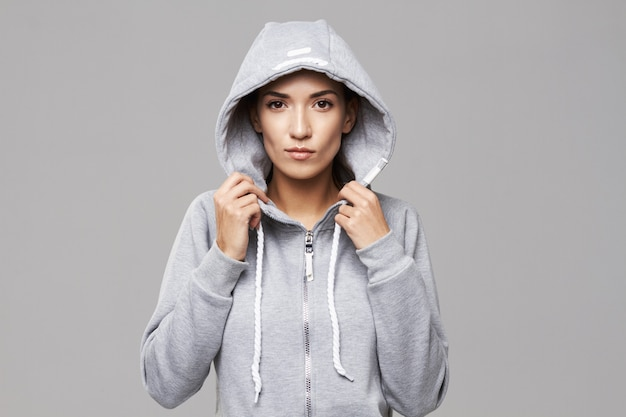 Ritratto della donna allegra brutale in cappuccio e abiti sportivi su bianco.