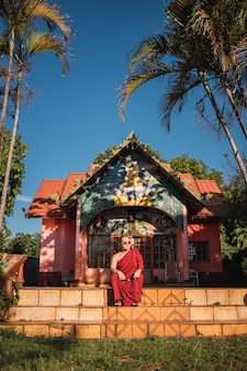 Portrait of a buddhist monk sitting in front of a small temple.