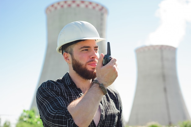 Portrait of a builder engineer with a radio set in his hand.
