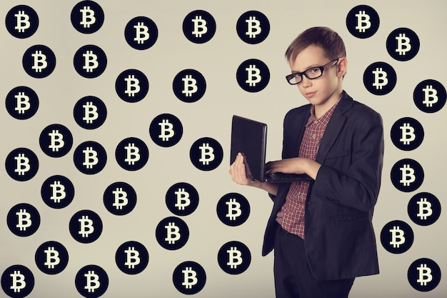 Portrait of business child in a suit and glasses earning virtual money in internet. young miner on bitcoins background, toned.