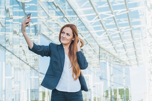 Portrait of a business girl, photograph myself on the phone, against the background of a modern glass business center.