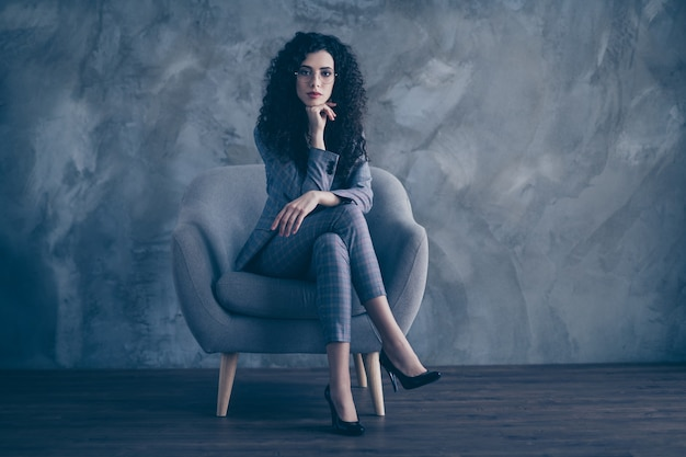 Portrait of business lady sitting in chair with crossed legs isolated over concrete wall