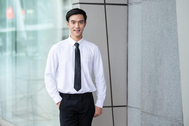 Portrait of business man, asian young male in white shirt smilling at office outdoor