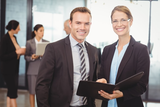 Portrait of business man and business woman holding file