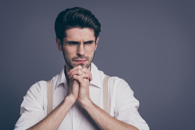 Portrait of business man holding arms together fingers crossed under chin deep minded making decision dressed formalwear white shirt suspenders specs .