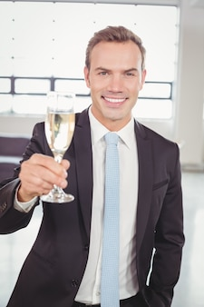 Portrait of business man holding champagne flute