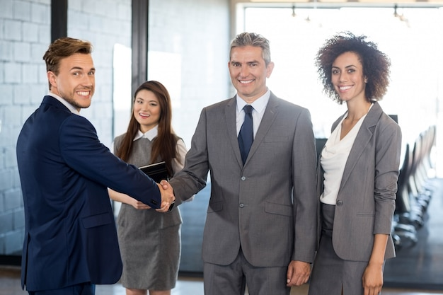 Portrait of business man interacting and shaking hands with team in office