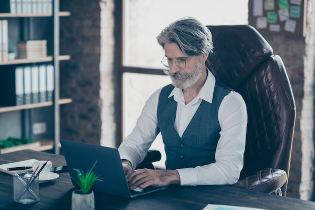 Portrait of business man typing on laptop in office