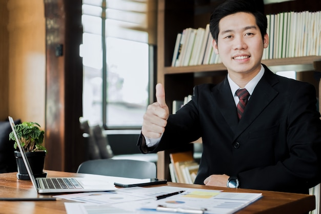 Portrait business people giving thumbs up in meeting room