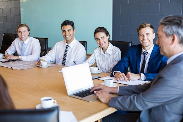 Portrait of business people sitting in conference room during a meeting in office