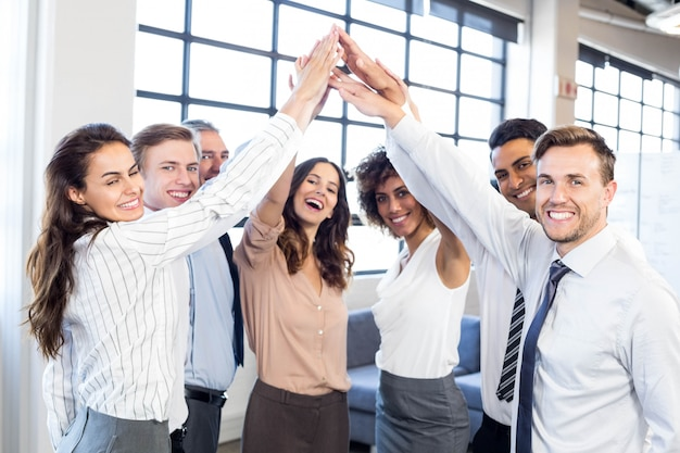 Portrait of business people stacking hands and smiling in office