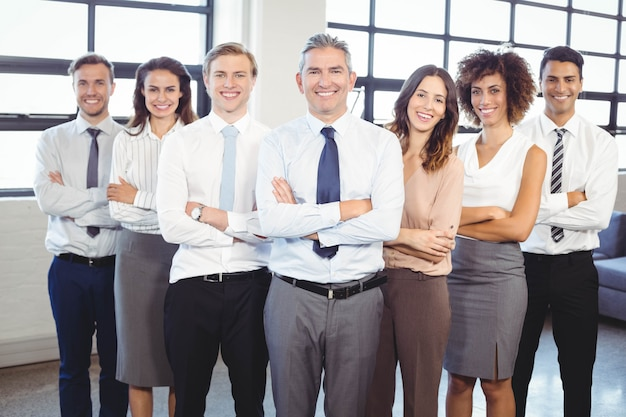 Portrait of business people standing with arms crossed in office