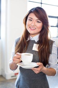 Portrait of business woman having a cup of tea in office