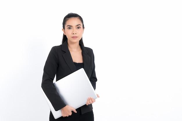 白い背景で隔離のスタジオショットで黒いスーツを着てラップトップを保持している肖像画のビジネス女性。かなり女性モデル。自信を持ってプロのサラリーマン。